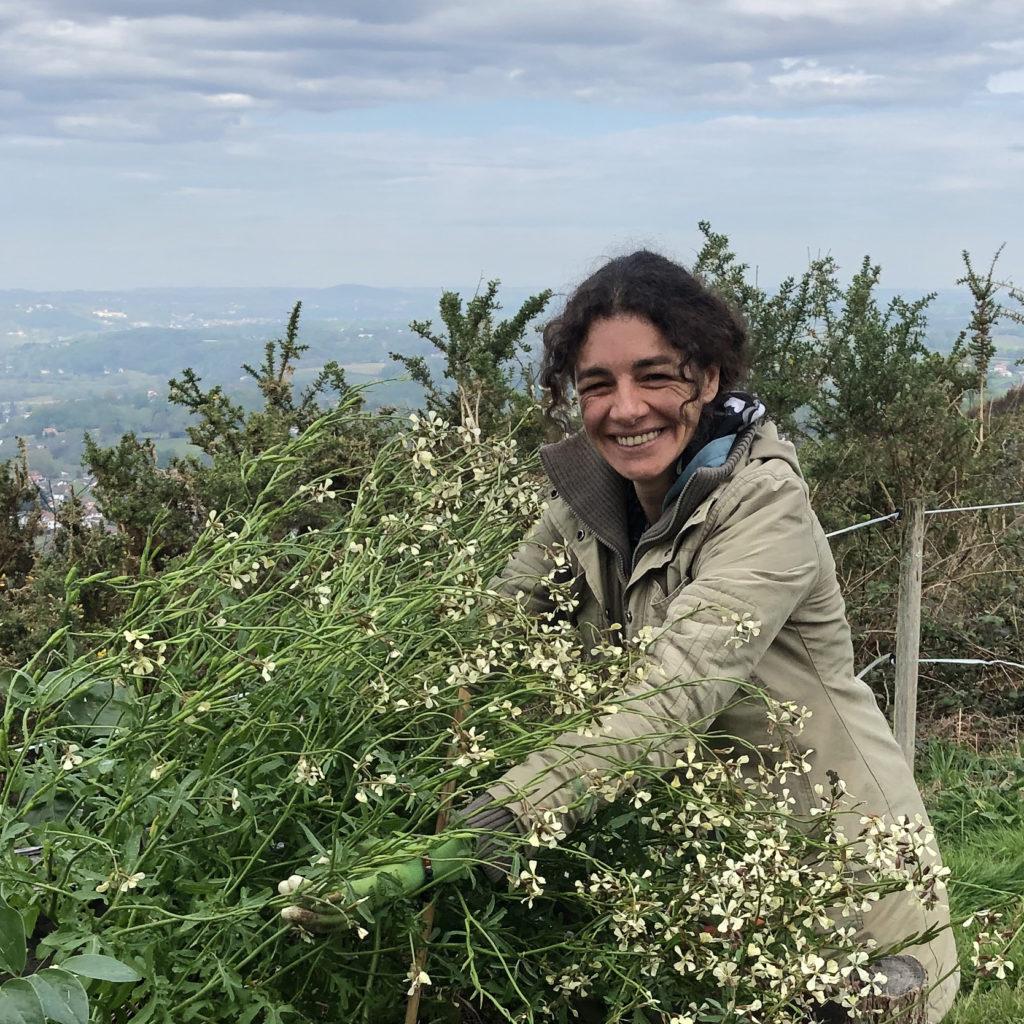 Photo d'Aurore, créatrice de KréAcor, au jardin des génies verts avec de la roquette dans les bras
